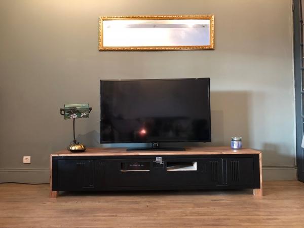Ce meuble au design industriel est issu d'une armoire industrielle anciennement utilisée comme vestiaire. Elle offre un grand volume de rangement. Les ouvertures créent dans la porte et la structure intérieure permettent d'avoir les décodeurs apparents et